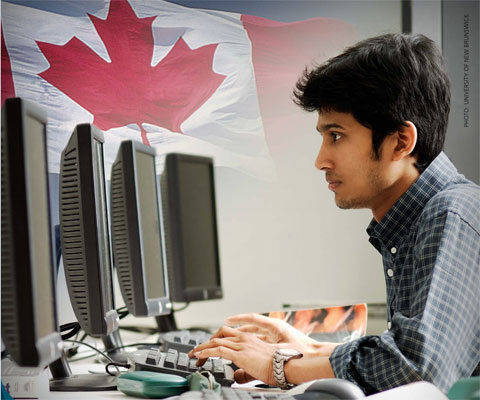 Indian student working in front of computers with Canadian flag in the background.