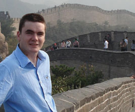 Canadian male student leaning on the Great Wall of China.