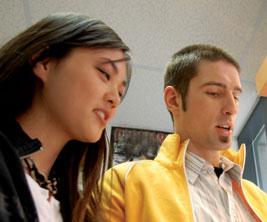 Un étudiant et une étudiante regardent un manuel scolaire