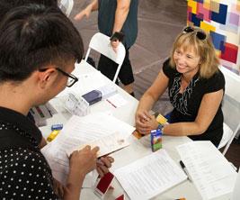 Étudiants discutent avec une employée d'une université à une foire étudiante.