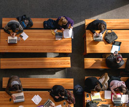 Aerial shot of students studying at long tables.