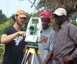 Canadian researcher with African colleagues looking at surveying tool in the bush.