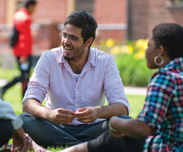 International students seated on the campus lawn.