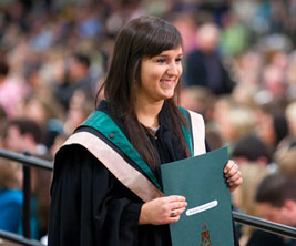 Fermale graduate holding a diploma at convocation ceremony.