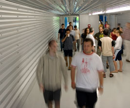 Students walking in a steel corrugated corridor.