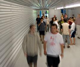 Des étudiants marchent dans un couloir en tôle d'acier ondulée.