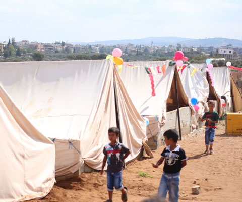 Little boys walking in a Syrian refugee camp.