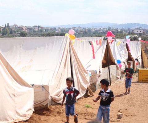 Petits garçons courent dans un camps de réfugiés syriens.