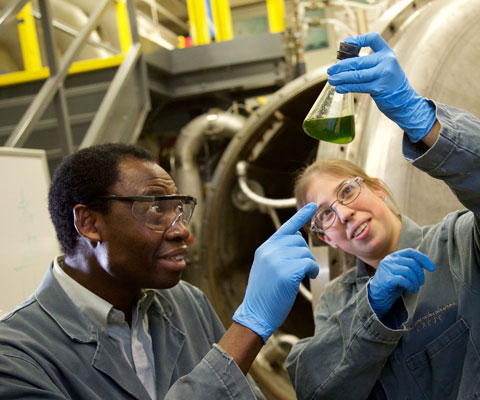 Two researchers looking at a flask of liquid in a lab.