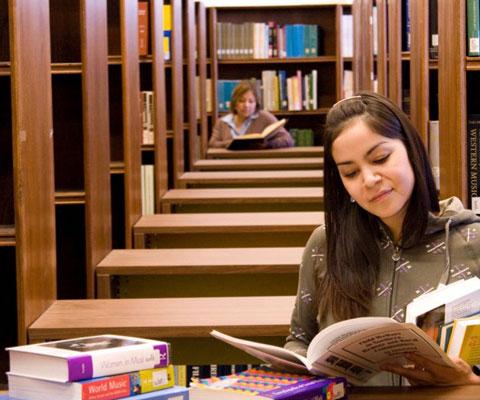 Étudiante autochtone qui lit un livre dans une bibliothèque.
