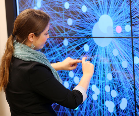 Female student touching an interactive screen on a wall.