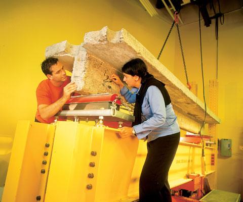 Deux chercheurs travaillent sur un bloc de ciment dans un laboratoire.