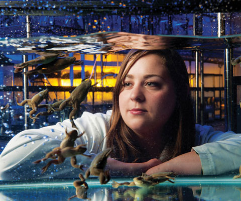 Female student looking at a tank of frogs.
