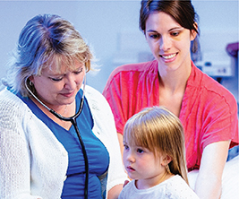 Two nurses examine young child