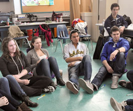 University students seated in a circle on the floor of a classroom.