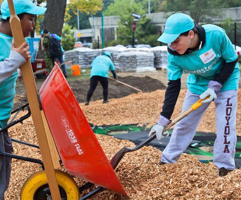 Des étudiants pellettent du paillis pour couvrir le sol.