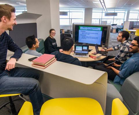 Étudiants étudient en groupe devant un grand écran.