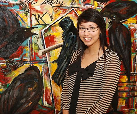 Étudiante universitaire autochtone devant une toile colorée.
