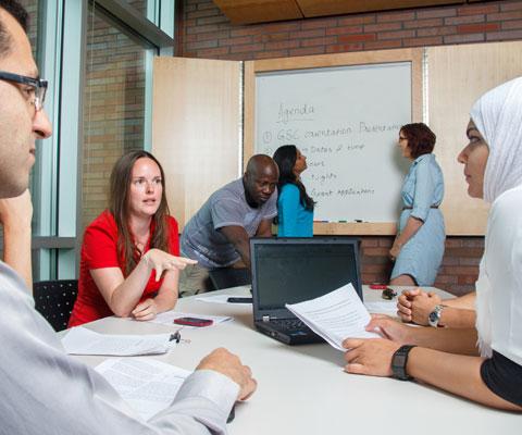 Étudiants de différentes cultures discutent autour d'une table avec tableau blanc en arrière-fond.