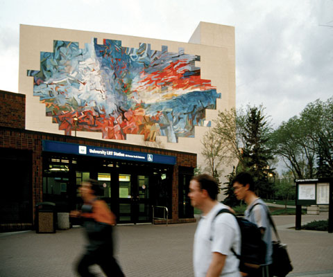 Student walking in front of building with an artistic mural.