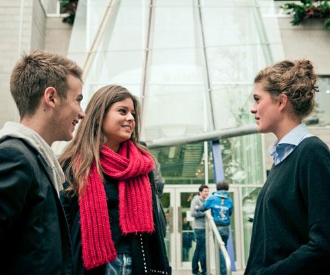 Deux étudiantes et un étudiant discutent devant un édifice moderne sur le campus de HEC Montréal.
