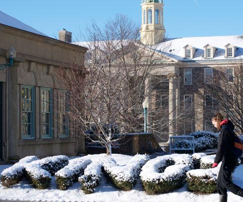 Une étudiante marche devant l'enseigne King's et des édifices sur le campus du King's University College pendant l'hiver.