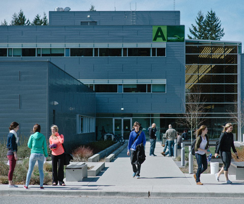 Students walking in front of modern blue building on University of the Fraser Valley.