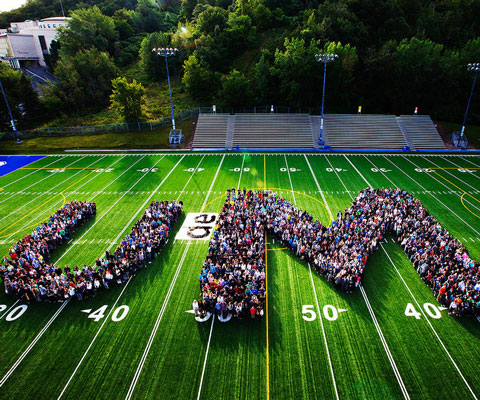 "Hundreds of students gathered on the football field, arranged in the shape of the letters ""U-M"""