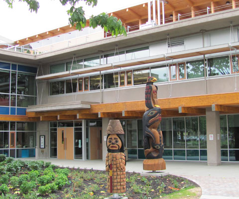 Modern campus glass building with two totem polls in front on Vancouver Island University campus.
