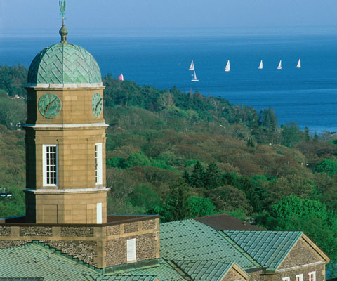 Tpwer of historic building of Dalhousie University with sailboats on the ocean in the background.