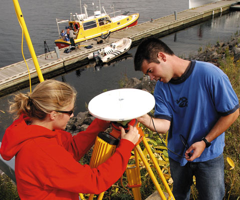Female and male researchers installing a dish instrument near the river in Fredericton, NB.