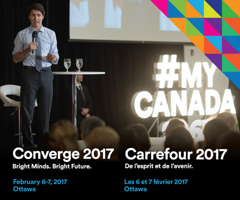 Prime Minister Justin Trudeau speaking to students at a Q&A session with #MyCanada sign lighted up in background - Converge 2017.