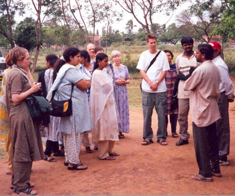 Canadian students and their Indian colleagues listen to a speaker in the countryside in India.