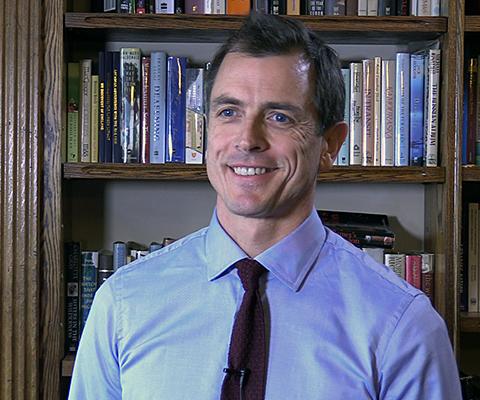Jonathon Breckton, directeur de l'Alliance for Useful Evidence à NESTA UK, assis devant une bibliothèque de livres.