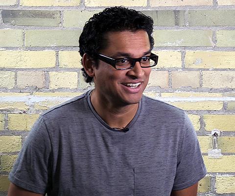Rocky Jain, directeur, technologies de réseaux mobiles & sociaux, Manulife, debout devant un mur en brique.