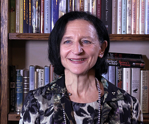 Sara Diamond, president of OCAD University, sitting in front of a bookshelf.