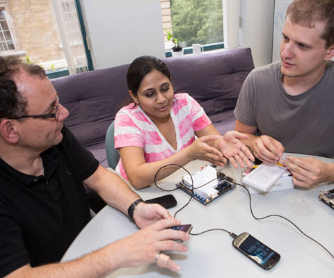 Professor Rose from the University of Toronto holding a mobile device while sitting at a table with two students to develop new mobile device applications.