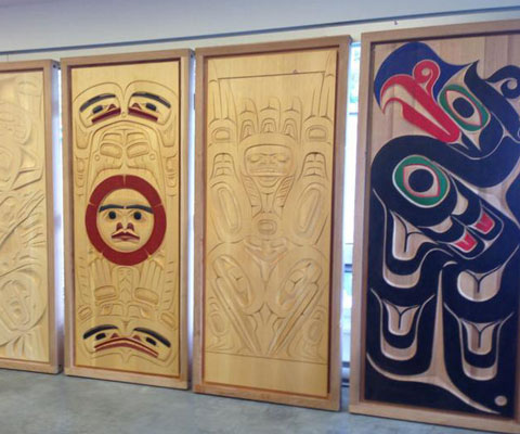 Four wooden doors stand upright to display traditional and contemporary Indigenous designs through different carvings and paintings.