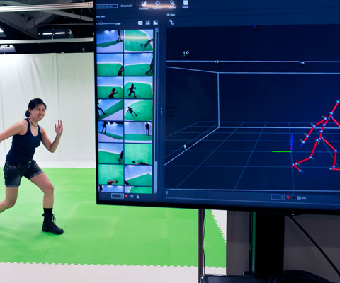 Female York student poses in a running stance in front of a green screen, while a computer in front of her captures her movements.
