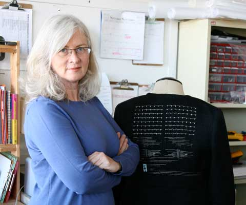 "Researcher and professor Barbara Layne poses with her arms crossed in front of her ""smart clothes"" technology."