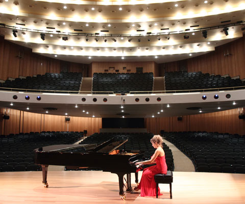Female student wearing a red ball gown rehearses her piano piece on stage in an empty theatre.