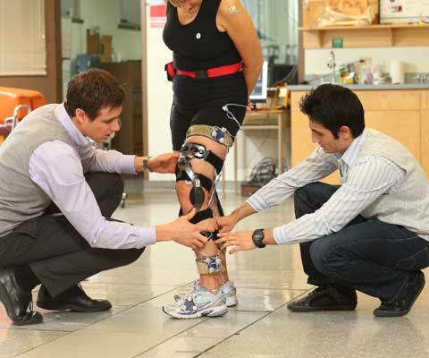 Two male researchers adjusting wires on the leg of a female runner.