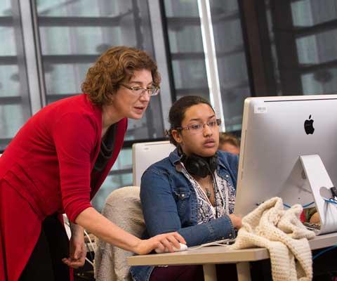 Une professeure enseigne à une étudiante devant un ordinateur Mac.