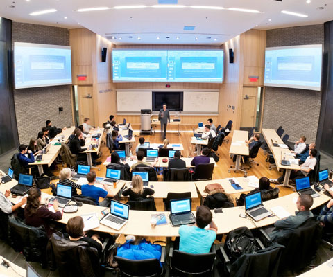 Students sit in a large lecture hall while listening to the professor at the front of the room.