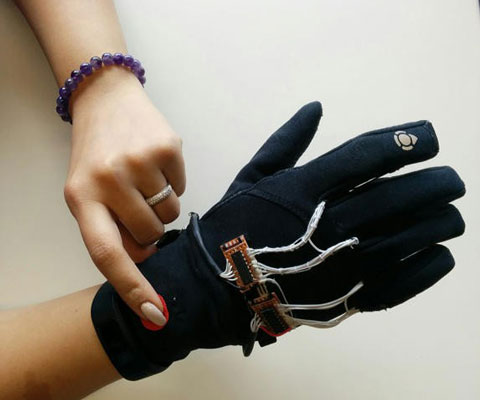 "A female student shows off a black ""Flex-N-Feel"" glove on her right hand and activates it by pressing a red button located on glove with her left hand."