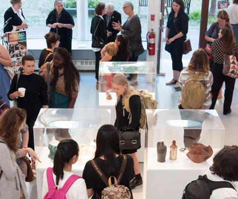 Des étudiants admirent des œuvres exposées sous des cloches de verre.