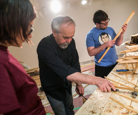 An Algonquin master canoe builder helps a male and female student assemble pieces of wood to build a birchbark canoe.