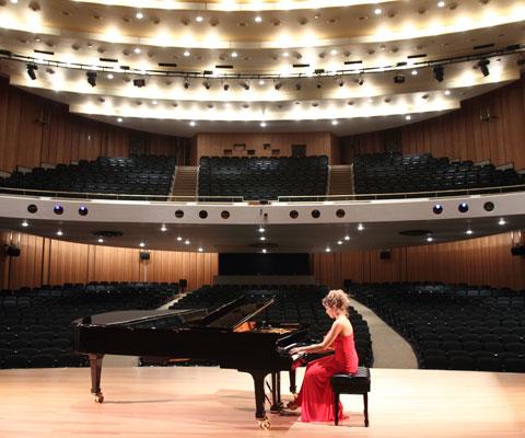 Une étudiante vêtue d'une robe de bal rouge répète son morceau de piano sur la scène d'un théâtre désert.