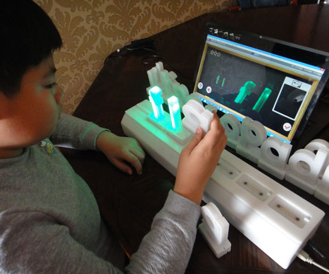 "A young boy sits at a table and spells out the world ""flag"" using green luminated as part of an innovative computer tool that helps dyslexic children learn how to read."