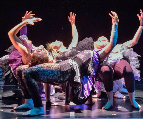 Five female dancers are shown under a spotlight on stage as they perform a dance routine.